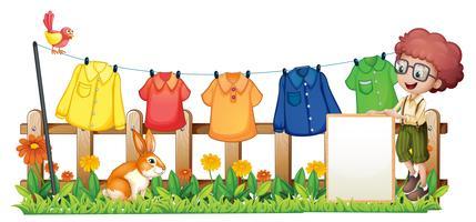 Un garçon tenant un cadre vide devant les vêtements suspendus vecteur