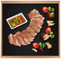 Steak et sauce épicée sur tableau noir