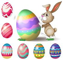 Un lapin poussant un gros oeuf de Pâques