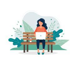 Femme avec ordinateur portable assis sur le banc