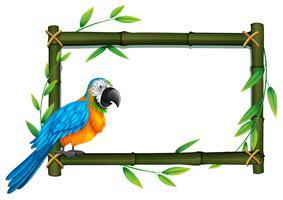 Un perroquet à la frontière de bambou vecteur