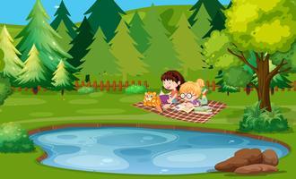 Deux filles lisant un livre au bord de l'étang