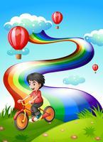 Un garçon fait du vélo au sommet d'une colline avec un arc-en-ciel