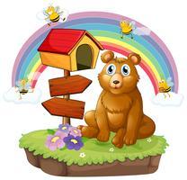 Un ours à côté d'une boîte aux lettres en bois et d'un panneau en bois
