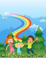 Une famille heureuse près des pins avec un arc en ciel dans le ciel