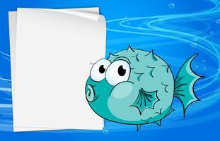 Un poisson à côté d'un papier sous la mer