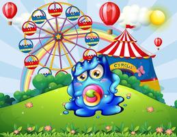 Un bébé monstre au sommet d'une colline avec un carnaval vecteur