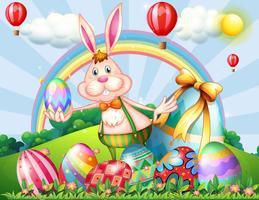 Un lapin au sommet d'une colline avec des oeufs de Pâques