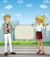 Un homme et une femme à la voie piétonne tenant un panneau vide