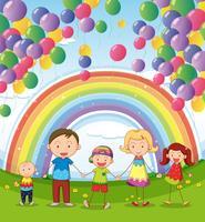 Une famille heureuse sous les ballons flottants avec un arc en ciel