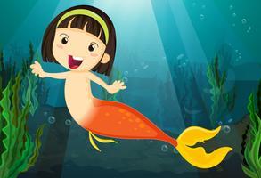 Une fille souriante sirène dans une eau