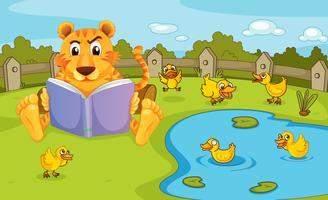 Un tigre lisant à côté d'un étang avec des canetons
