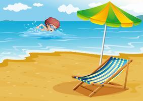 Un garçon nageant à la plage avec une chaise et un parapluie