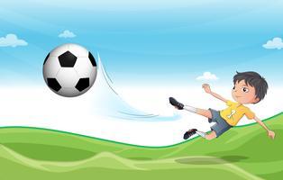 Un garçon jouant au football sur les collines