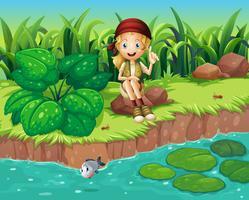 Une fille assise au rocher au bord de la rivière