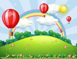 Ballons flottants au sommet d'une colline avec un arc-en-ciel