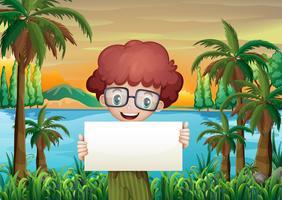 Un garçon souriant tenant un panneau vide vecteur