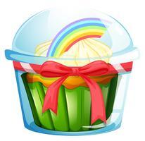 Un récipient avec un petit gâteau à l'intérieur décoré avec un ruban