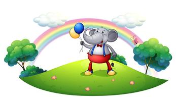 Un éléphant avec des ballons au sommet de la colline