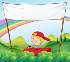 Un garçon dans sa voiture sous un panneau vide