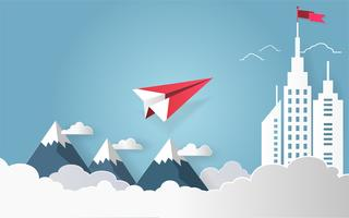 Concept de leadership, avion rouge volant sur ciel avec nuage sur la montagne et bâtiment architectural avec un drapeau sur le dessus.