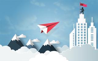 Concept de leadership, avion rouge volant dans le ciel avec nuage au-dessus de la montagne et bâtiment architectural avec homme au sommet tenant le drapeau.