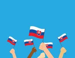Mains tenant des drapeaux de Slovaquie isolés sur fond bleu