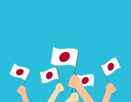 Mains d'illustration vectorielle tenant des drapeaux du Japon sur fond bleu vecteur
