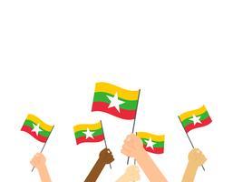 Mains d'illustration vectorielle tenant des drapeaux du Myanmar sur fond blanc vecteur
