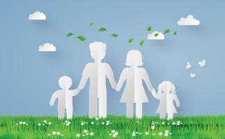 famille de papier sur le champ d'herbe