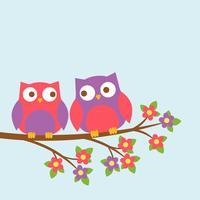 Couple de chouettes mignons sur une branche en fleurs