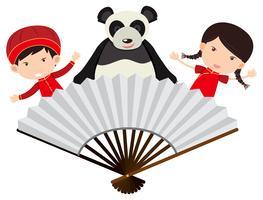 Chinois garçon et fille avec panda derrière le ventilateur