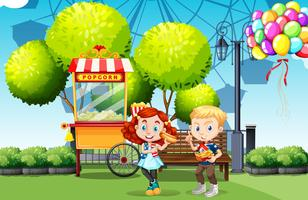 Garçon et fille mangeant dans le parc vecteur
