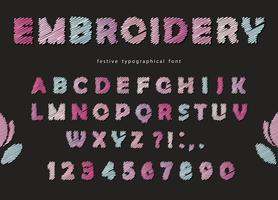 Conception de polices de broderie. Lettres et chiffres ABC mignons en couleurs pastel sur fond noir.