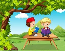 Deux garçons lisant des livres dans le parc