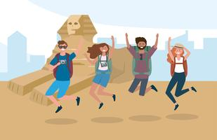 Touristes femmes et hommes sautant devant des pyramides égyptiennes