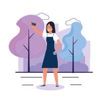 Jeune femme avec smartphone prenant selfie dans le parc