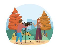 Journaliste parlant avec un caméraman dans un parc urbain