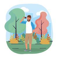 Jeune homme urbain à la barbe avec smartphone dans le parc