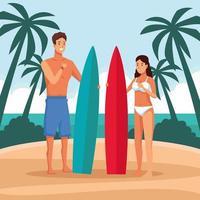 Jeune couple à la plage avec des planches de surf