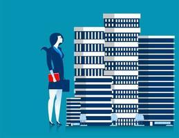 Propriétaire de femme d'affaires debout à côté des bâtiments