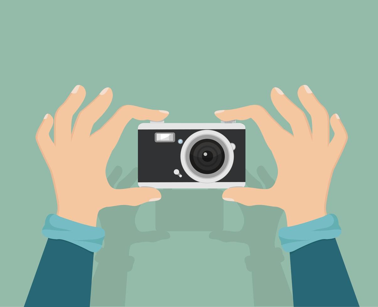 mãos segurando uma câmera retro vetor