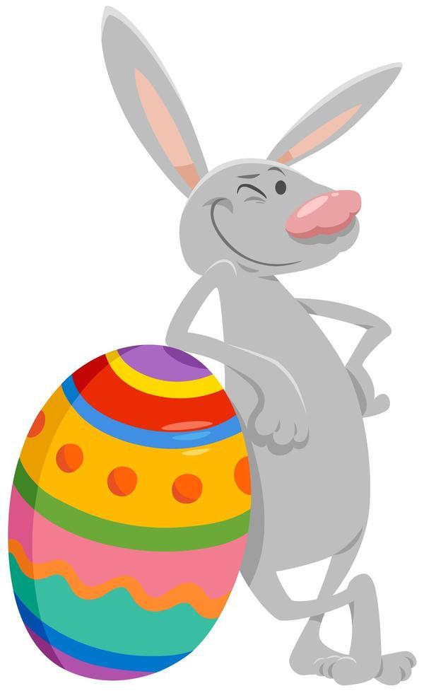 desenho animado coelhinho da Páscoa com grande ovo colorido vetor