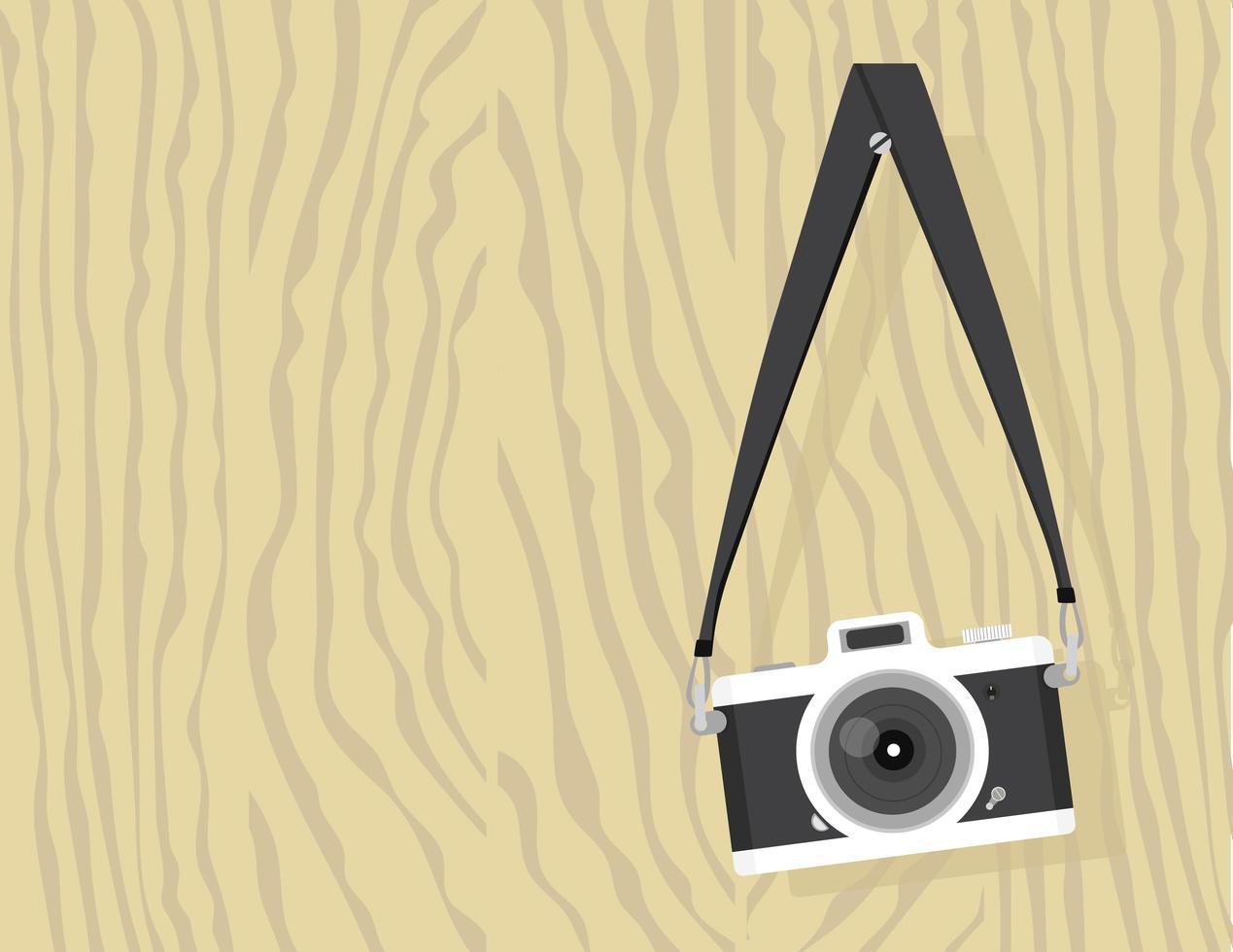 câmera vintage pendurada em um parafuso em uma placa de madeira vetor