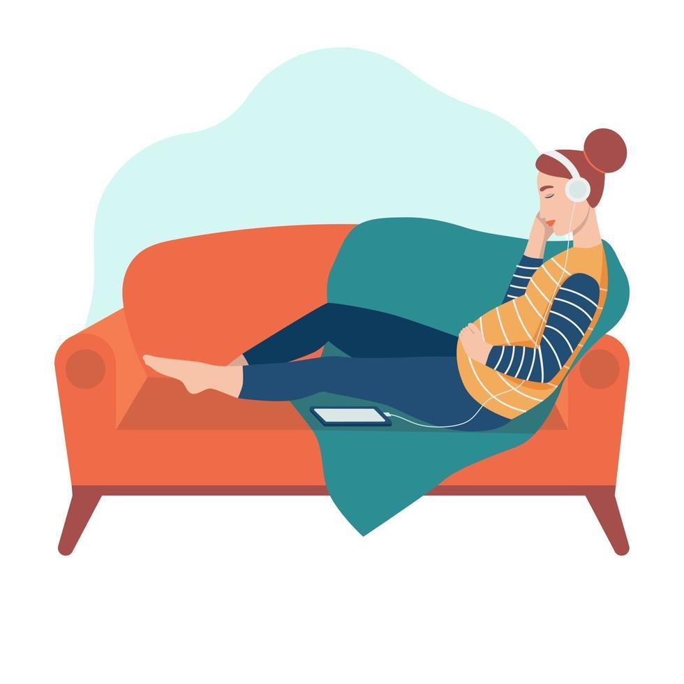 uma mulher grávida se senta no sofá e ouve música com fones de ouvido vetor