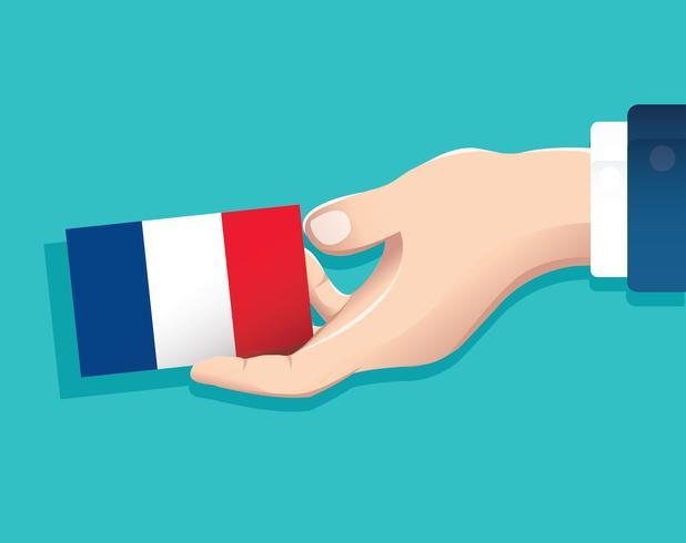 mão segurando o cartão de bandeira de França com fundo azul vetor