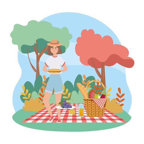 Mulher no piquenique com sanduíche e cesta vetor