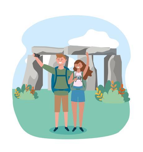 Casal tirando foto na frente de stonehenge vetor