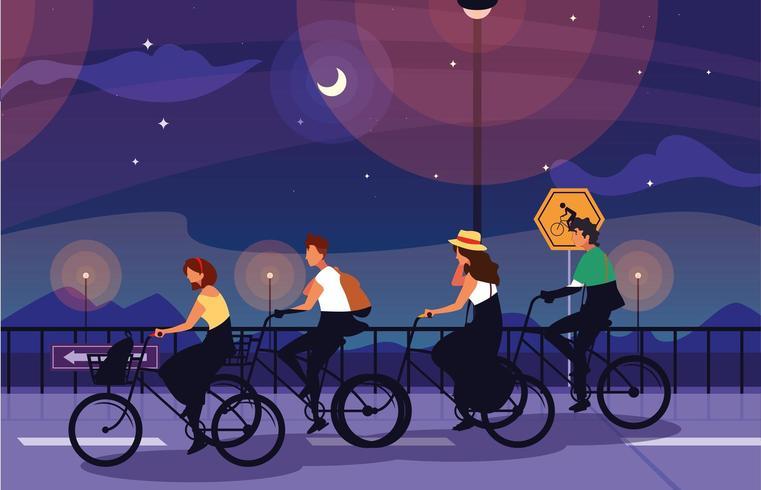 pessoas andando de bicicleta à noite vetor