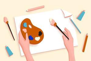 mãos femininas com pincel, tinta e lápis